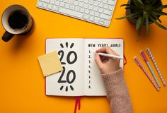 Free Stock Photo Of A Young Woman Hand Writing In A 2020 New Year Notebook With List Of Resolutions And Objects Royalty Free Stock Photos - 164009018