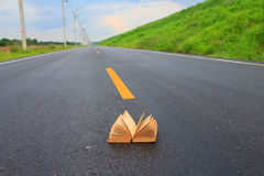 Stock Photo - Open book on road outdoors Royalty Free Stock Photos