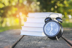 Stock Photo:Retro alarm clock and books on wooden table and Mor Royalty Free Stock Image