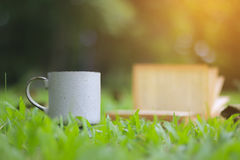 Stock Photo:Retro cup of coffee with book  on the green grass Royalty Free Stock Photography