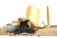 Stock Photo:Roasted coffee beans, old book and cup of coffee ba Royalty Free Stock Photo