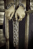 Stock Photo:Rusty chains, shackles binding the hands of a prett Stock Photos