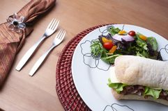 Stock Photo of a sandwich on a plate. Sandwich on white plate with a set table Royalty Free Stock Photos
