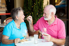 Stock Photo of Senior Couple on Date. Senior couple on romantic lunch or dinner date.  He's feeding her the appetizer by hand Royalty Free Stock Photo