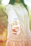 Stock Photo:Soft focus of happy girl holding in hand bottle of Royalty Free Stock Photos