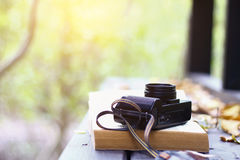 Stock Photo:Still life in the forest with camera and book. Hori Royalty Free Stock Photos