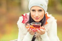 Stock Photo: Young attractive woman holding in hand hot red tea. Relaxing in autumn nature with hot tea Royalty Free Stock Photo