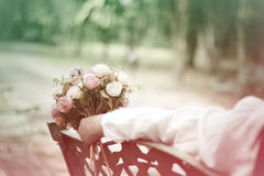 Stock Photo:young girl sitting on a bench in a large bouquet of Stock Photo