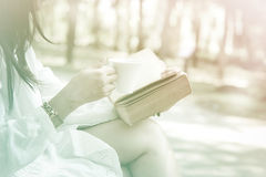 Stock Photo:Young woman reading book and drinking coffee to go Royalty Free Stock Image