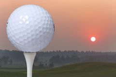 This is a stock photograph of a golf ball. A closeup of a golf ball on a tee at sunrise Royalty Free Stock Image