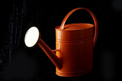 Stock photograph of an orange watering can. An orange watering can on a black background Royalty Free Stock Photos