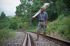 Stock photograph of South African entrepreneur small business broom salesman on railway line Stock Photos