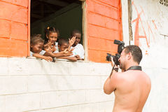 Stock Photographer At Work. Santa Rosa, Ecuador - 26 July 2015: Photographer Taking A Picture Of A Group Of Afro American Children On The School Window In Santa stock image