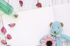 Stock Photography flat lay vintage white painted wood table purple flower petals bear doll green glass bottle royalty free stock photos
