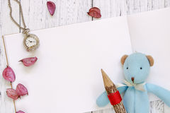 Stock Photography flat lay vintage white painted wood table purple flower petals bear doll holding pencil stock images