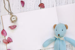 Stock Photography flat lay vintage white painted wood table purple flower petals bear doll pocket clock royalty free stock image