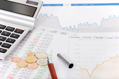 Stock quotes, calculator and money on desk. Stock quotes, charts, tables, calculator and money on a desk Royalty Free Stock Photography
