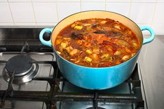 Stock simmering gently in a pot on a gas stove Stock Images