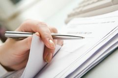 Stock-taking. Close-up of  hand holding pen with paper over pile of documents Stock Photography
