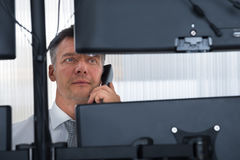 Stock Trader Looking At Multiple Computer Screens. Mature male stock trader using telephone while looking at multiple computer screens at office stock photos