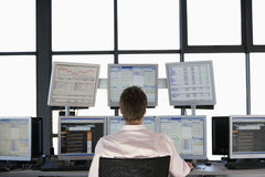 Stock Trader Looking At Multiple Computer Screens. Rear view of stock trader looking at multiple computer screens Royalty Free Stock Image