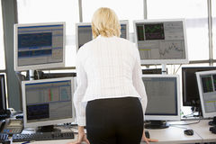Stock Trader Looking At Multiple Monitors Royalty Free Stock Images
