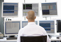 Stock Trader Looking At Multiple Monitors. At work royalty free stock photography