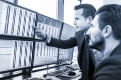 Stock traders looking at market data on computer screens. Businessmen trading stocks. Stock traders looking at charts, indexes and numbers on multiple computer Stock Photo