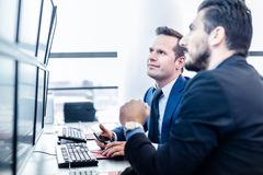 Stock traders looking at market data on computer screens. Successful businessmen trading stocks. Stock traders looking at graphs, indexes and numbers on Royalty Free Stock Images