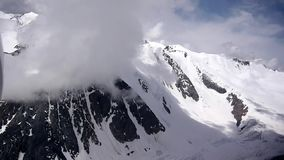 Stock Video Footage Flying through the clouds glacier mountain. Plane flies directly to the cloud, swerves and we see the glacier. Alpine flying 4,000 meters stock footage