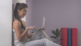 Girl with a laptop in the gym. Stock video footage girl sitting in the gym with a laptop stock images