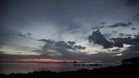 Stock Video Footage 4K pink stripe horizon sunset lake island timelapse. Above the beach hlomikami Eska gusteyut twilight, the sun sets over the a small island stock video