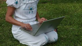 Stock Video Footage 1920x1080, 1080p, hdv, Woman in white with a laptop on his knees, working. Woman  sitting on the grass lawn, Freelance, Summer park, female stock video footage