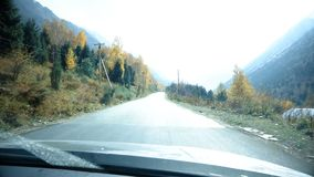 Driving Up The Snowy Mountains. In this stock video, the shot shows the point of view of driving a vehicle that is going up the snowy mountains. This video can stock footage