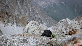 A backpack rests among the rocks. This stock video shows beautiful footage of mountain rocks. This video can be used in documentaries, commercials and other stock video
