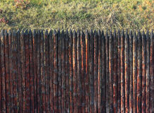Stockade fence. Old wooden sharpened palisade for defence Stock Image
