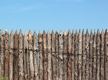 Stockade wooden fence on blue sky background.  Royalty Free Stock Photo