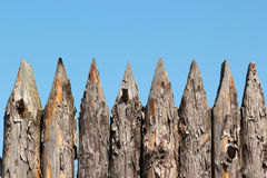Stockade wooden fence on blue sky background.  Stock Photography