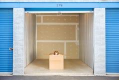 Stockage : Femme jetant un coup d'oeil pour dégrossir hors de la boîte dans l'unité Photo stock