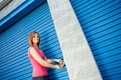 Stockage : Femme mettant la serrure sur la porte d'unité Photo stock