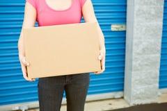 Stockage : La femme avec la boîte se tient prêt la porte Image stock