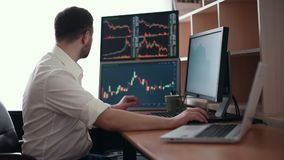 Stockbroker in white shirt is working in a monitoring room with display screens. Stock Exchange Trading Forex Finance stock video footage