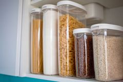 Stocked kitchen pantry with food - pasta, buckwheat, rice and sugar . The organization and storage in kitchen of a case with grain. In plastic containers stock images