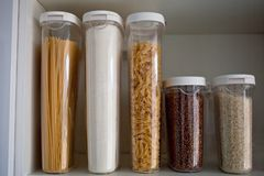 Stocked kitchen pantry with food - pasta, buckwheat, rice and sugar . The organization and storage in kitchen of a case with grain. In plastic containers royalty free stock photos