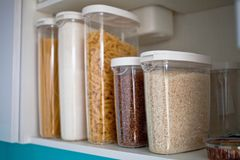 Stocked kitchen pantry with food - pasta, buckwheat, rice and sugar . The organization and storage in kitchen of a case with grain. In plastic containers royalty free stock images