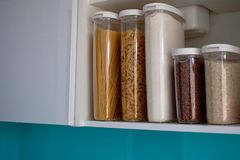 Stocked kitchen pantry with food - pasta, buckwheat, rice and sugar . The organization and storage in kitchen of a case with grain. In plastic containers stock photos