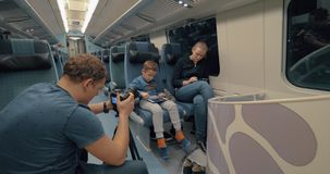 Stocker making footage of family train journey. Man stocker shooting footage of a mother with son traveling by express train and passing time with pad and stock footage