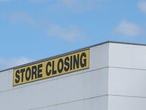 Stockez le noir fermant sur les lettres jaunes sur un bâtiment industriel claded par blanc photos stock