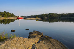 Stockholm archipelago: moored red sailingboat in natural harbour Royalty Free Stock Photo