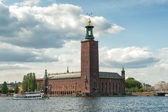Stockholm City Hall. Stockholm, Sweden - July 27, 2011: A tour boat passes iconic Stockholm City Hall. Stockholm City Hall which was completed in 1923 is the royalty free stock images